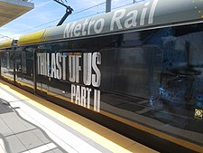 "A train with an advertisement for the game: the large block text says ""The Last of Us Part II"", with a dark picture of Ellie's face."