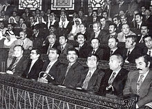 Grande gruppo di uomini seduti in fila