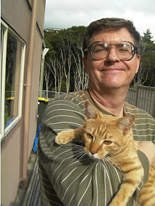 Picture of a man holding a kitty cat.