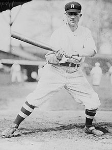 "A man in a white baseball uniform with dark pinstripes, high dark socks, and a dark cap with a ""R"" on the front stands leaning to the right with his bat out to his left side."