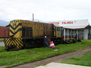 Rail transport in Honduras - Passenger train in La Ceiba on January 11, 2005. Engineer tanks fuel manually from a barrel. Colorful passenger car (former box car without walls) is attached to the right.
