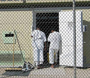 Guantanamo Bay detainee uniforms - Image: Two detainees in white stand in the doorway of their bay in Camp 4