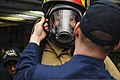 U.S. Sailors newly assigned to the aircraft carrier USS Nimitz (CVN 68) help one another don firefighting equipment aboard the ship 130117-N-KE148-107.jpg