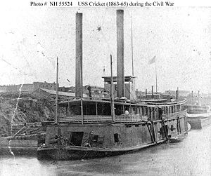 "USS Cricket (1863-1865, ""Tinclad"" # 6) Tied up at a Western Rivers city, during the last years of the Civil War, with a barge astern and a boat alongside. Note the decorative star suspended between her smokestacks."
