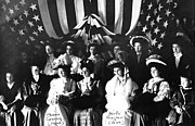 picture of about 14 formally dressed women in 1908 posing with a draped flag in the background
