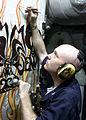 US Navy 030402-N-5027S-004 Machinist's Mate 3rd Class Jamie Eichenlaub from Williamsport, Penn., paints a mural on a quick acting watertight door.jpg
