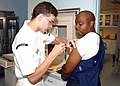 US Navy 030620-N-7535G-021 Hospital Corpsman 3rd Class Brendan Greene gives Aviation Electrician's Mate 2nd Class Mark A. Swann a Typhoid shot during a visit to medical.jpg