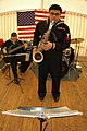 US Navy 041215-N-3236B-009 Musician 2nd Class Jeremy Bustillos, a saxophone player in the Commander Sixth Fleet Jazz Ensemble, entertains World War II veterans, active duty Soldiers and Sailors during a luncheon honoring the li.jpg