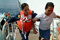 US Navy 050330-N-6504N-002 Hospital Corpsman 3rd Class Lynette Shute, left, helps an East Timorese woman up a boat ramp.jpg