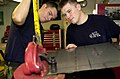 US Navy 050831-N-1730J-011 Aviation Structural Mechanic 3rd Class Matt Bahlmann, and Aviation Structural Mechanic 3rd Class Kevin Thompson, use a throat sheer cutting tool to slice sheet metal.jpg