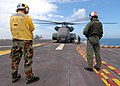 US Navy 050926-N-8933S-005 A crew chief assigned to Helicopter Mine Countermeasures Squadron Fourteen (HM-14), monitors the loading of his MH-53E Sea Dragon helicopter as it prepares to depart the flight deck of the amphibious.jpg