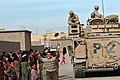US Navy 051125-N-9885M-560 Iraqi children in Khan as Sur, Iraq, gather around a U.S. Army M3A3 Bradley tank, from 3rd Armored Cavalry Regiment, Tiger Squadron, Predator Troop, as Iraqi Army Soldiers distribute supplies.jpg