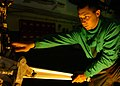 US Navy 051204-N-3488C-029 Aviation Structural Mechanic Airman Jermaine Ebert inspects the launch bar and nose landing gear of one of his squadron's F-A-18F Super Hornets.jpg