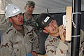 US Navy 090302-N-4245W-022 Petty Officer 3rd Class Joe Nichols, right, and Ensign Matthew King, both assigned to Amphibious Construction Battalion 2, test the air conditioning unit in a barracks tent.jpg