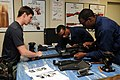 US Navy 090304-N-4205W-131 Special Warfare Boat Operator 1st Class Raul Madrigal instructs Police Constable Henry Sharm-Mion and Able Seaman Julio Charles on the correct assembly of a M19 grenade machine gun.jpg
