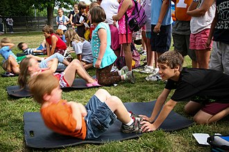 Calisthenics - School children perform sit-ups, a common type of calisthenic, during a school fitness day.