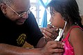 US Navy 090829-N-9689V-004 U.S. Public Health Service oncologist Capt. Otis Brawley allows a child to listen to her own breathing during a Pacific Partnership 2009 medical civic action project.jpg