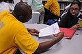 US Navy 091029-N-6220J-016 Aviation Boatswain's Mate (Fuels) 1st Class Ulric Carter reviews a young girl's reading homework at the Finnigan Park Boys and Girls Club.jpg