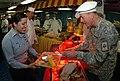 US Navy 091126-N-2688M-097 Gen. David H. Petraeus, commander, U.S. Central Command, serves turkey to Logistics Specialist 3rd Class Albrian Crisostomo during Thanksgiving dinner aboard the aircraft carrier USS Nimitz (CVN 68).jpg
