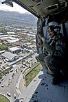 US Navy 100116-N-6006S-081 An aircrew chief from Helicopter Sea Combat Squadron (HSC) 9, surveys the city of Port-au-Prince before landing.jpg