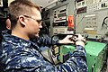 US Navy 100505-N-6935K-004 Aviation Electrician's Mate 3rd Class Shane Rogers checks a power supply unit for aircraft.jpg