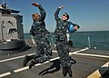 US Navy 110508-N-NL541-139 Seaman Michael Trusik and Seaman Arthur Miller celebrate after completing a successful anchoring detail off the coast of.jpg
