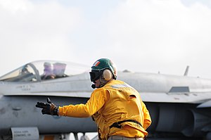 US Navy 111231-N-GZ832-182 Lt. Blake Whetstone, assigned to the air department aboard the aircraft carrier USS Carl Vinson (CVN 70), signals for th.jpg