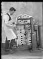 Unidentified railway employee using an electric rivetter at the Hillside Railway Workshops, 1926 ATLIB 299953.png