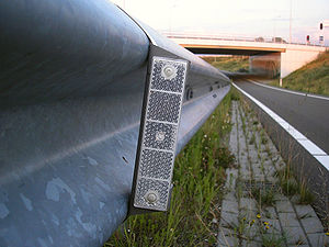 English: Roadside reflector on guard rail alon...