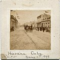 View of cavalry officers from the First North Carolina Volunteer Regiment riding down the middle of a street in downtown Havana, Cuba, on January 1, 1899. Crowds are seen lining the road as American (28877047925).jpg