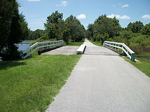 Inverness, Florida - The Withlacoochee State Trail crosses an old railroad bridge over part of Henderson Lake.