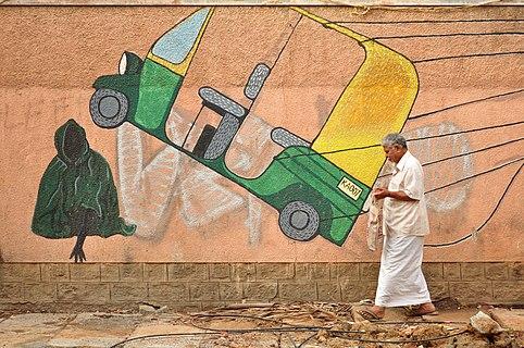 A man walks past a wall graffiti in Bangalore, India