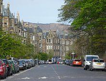 Une grande avenue bordée d'immeubles en pierre grise sur la gauche et d'arbres sur la droite