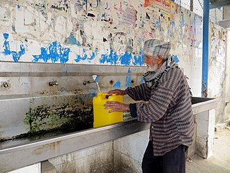 Water supply and sanitation in the Palestinian territories - An elderly man fills a water container at a public multi-faucet sink in Khan Younis, Gaza Strip.