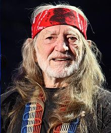 A red Headed man with white beard smiling. He wears a red bandanna, a black shirt and a red, white and blue guitar strap.
