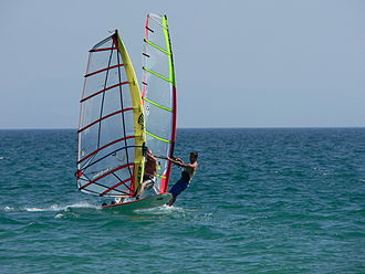 Windsurfing - The windsurfer in the foreground is using a camber induced sail and is fully planing using the footstraps, while the other is using a rotational sail and is not planing.