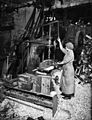Woman operating boring machine; boring wooden reels for winding barbed wire.jpg