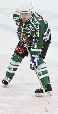 Zigmund Palffy in a full hockey uniform holding his stick out on the ice rink