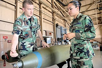 19th Weapons Squadron - Major William Fry, 19th Weapons School instructor and director of operations, explains to Senior Airman Brandi Gilstrap about the specs of an air-to-ground munition