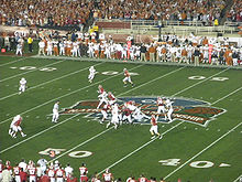 American football players in formation at the 50-yard line on a green field.