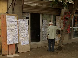 Real estate economics - A customer perusing real estate listings at an agent's office in Linxia City, China
