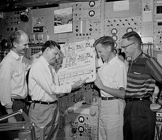 "Lawrencium - Albert Ghiorso updating the periodic table in April 1961, inscribing the symbol ""Lw"" in the position for element 103, as codiscoverers Latimer, Sikkeland, and Larsh (left to right) look on approvingly."