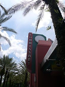 "A photograph of a red building with a sign reading ""COMMISSARY"" in vertical letters all surrounded by palm trees under a blue sky with white clouds"