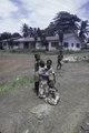 ASC Leiden - F. van der Kraaij Collection - 01 - 008 - Saye Town. Elementary school pupils one carrying a child in front of a modern house - Monrovia, Sinkor, Montserrado County, Liberia, 1976.tiff