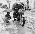 A little girl holding an umbrella watches a despatch rider attempt to clear the carbuerettor of his motorcycle in torrential rain, 4 October 1943. NA7526.jpg