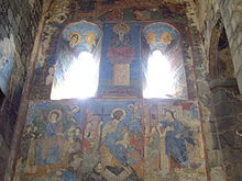 Colourful paintings of saints on the stone walls and inside the arches.