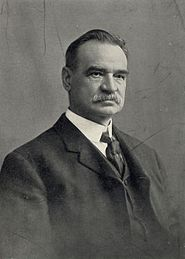 A black-and-white photo of a mustachioed man wearing a dark Victorian-style suit and tie and white shirt