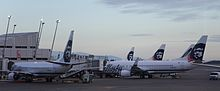Early morning photo showing Alaska Airlines aircraft parked at an airport terminal, with jet bridges connected to the planes. Five aircraft can be seen in the photo.