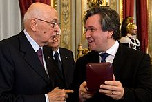 immagine di uomo anziano alla presentazione di un uomo più giovane a destra con un premio sinistra