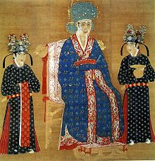 A square painting of a woman in an intricately decorated blue dress and a large blue hat, sitting in a throne. She is flanked by two female attendants in black dresses with flower covered black hats.